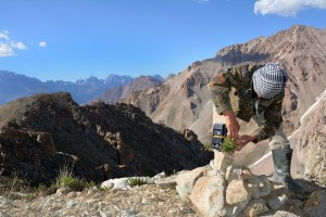 A field assistant places a camera high in the Iskanderkul Pass, ideal snow leopard habitat. Photo by Tara Meyer.